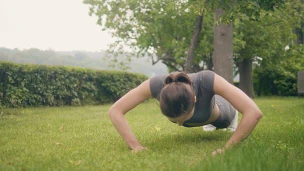Sportovní žena školení push up cvičení na trávě v letním parku