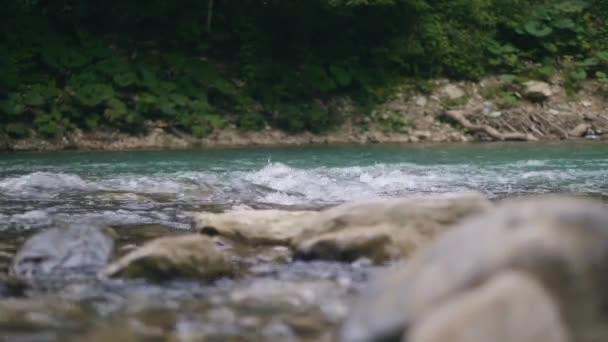 Proud vody z horské řeky rychle teče po kamenech. Čistá voda v potoce