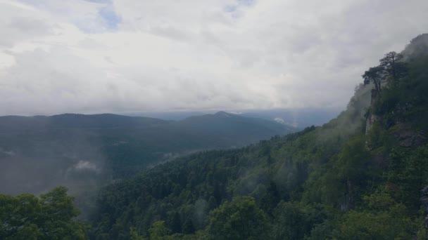 Zelené hory a mraky v obloze. Horské vrcholy údolí a v mlžným oparem