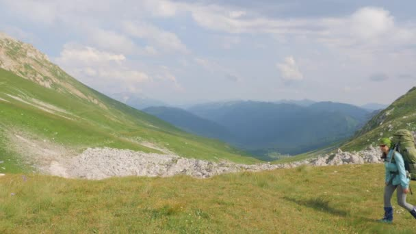 Hiking woman with backpack traveling in mountain. Summer climbing and tourism