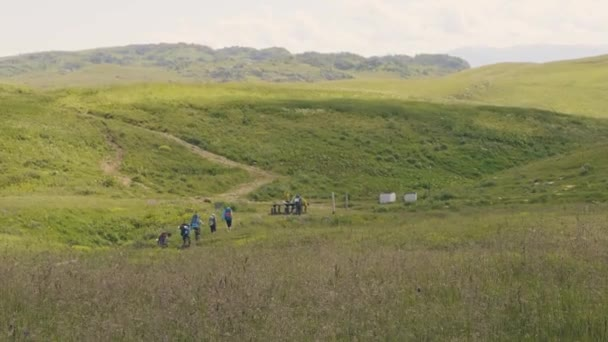 Tourist people with backpacks hiking on green meadow in mountain hills