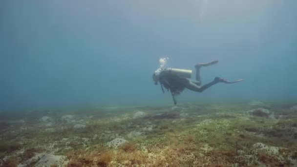 Scuba diver floating on sea bottom and waving hand to camera, underwater view