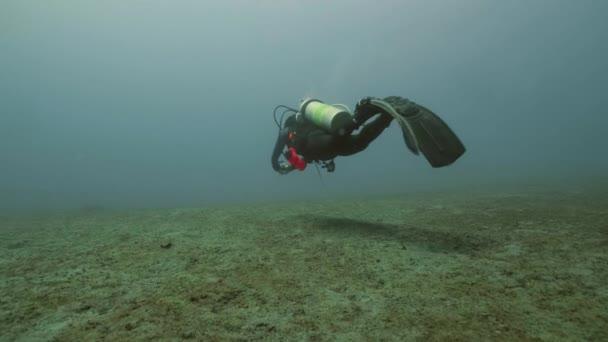 Scuba diver galleggiante sul fondo del mare, vista subacquea. Concetto di immersioni di mare profondo