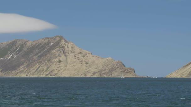 Hory krajina a plachty lodí v modré moře. Plachetnice v moři na horách