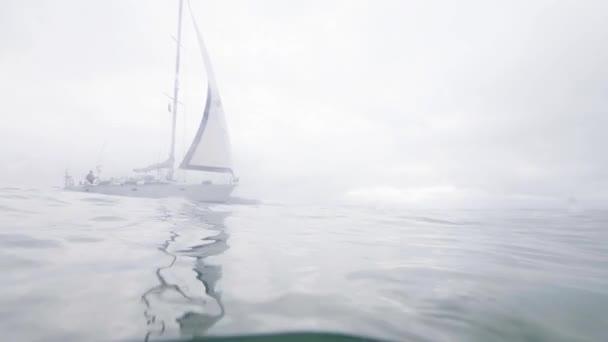 Zobrazit čáry ponoru vyplutím jachty v mořské vodě na zamračená obloha pozadí