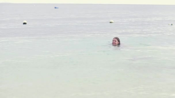 Young woman swimming in sea water while summer vacation. Tourist woman swimming in ocean at summer resort on tropical beach.