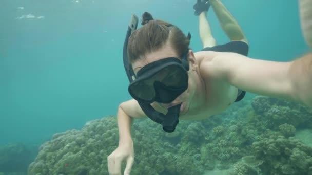 junger Mann bläst Schnorchelmaske, um beim Tauchen im Meer den Druck in den Ohren auszugleichen. Mann dreht Selfie-Video beim Tauchen auf Maske und Schlauch am Korallenriff.