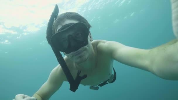 junger Taucher bläst Schnorchelmaske, um beim Tauchen im Meer den Druck in den Ohren auszugleichen. Mann dreht Selfie-Video beim Unterwasserschwimmen mit Maske und Schnorchel im blauen Ozean.