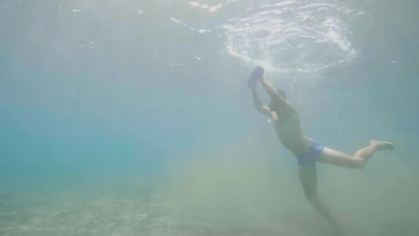 Mann macht Übungen mit Kurzhanteln unter Wasser.