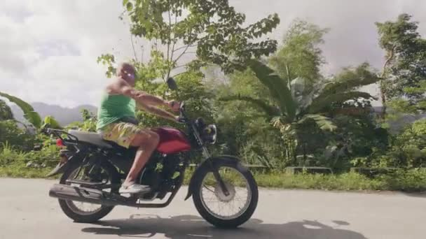 Mature man motorcyclist riding on motorbike on countryside road on tropical palm trees landscape. Senior man traveling motorcycle on road in summer moto trip.