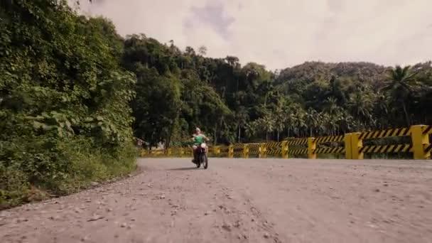 Dospělý muž jede na motorce po silnici na tropické lesní krajině. Senioři jezdíš na motorce, když je v letní dovolené. Životní styl motocyklů.