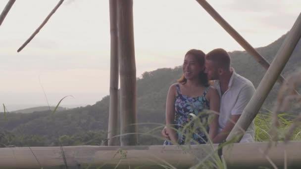 Romantický pár si užívá horské krajiny, když se líbánky. Šťastný muž a žena, kteří se objímali romantickou datli na tropické horské pozadí.