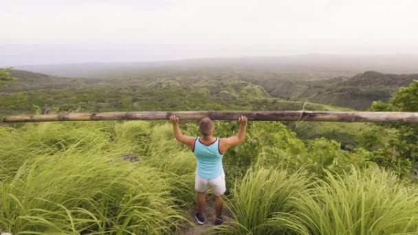 Sport man doing press exercise with heavy wooden barbell on green hill landscape. Athlete man using timber bar for lifting weight on outdoor workout. Fit man training in tropics.