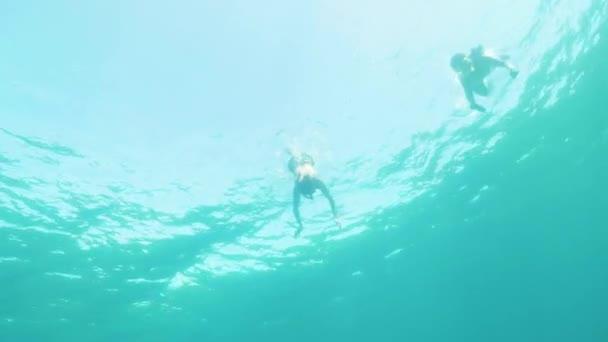 Mädchen und Junge schwimmen zusammen unter Wasser und schnorcheln im Ozean.