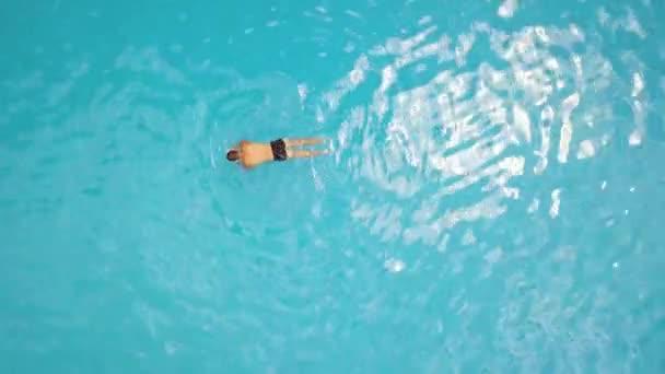 Drone vista hombre nadando en la piscina de agua azul en el hotel del complejo. Vista aérea hombre nadador nadando en la piscina al aire libre en las vacaciones de verano en el hotel turístico.