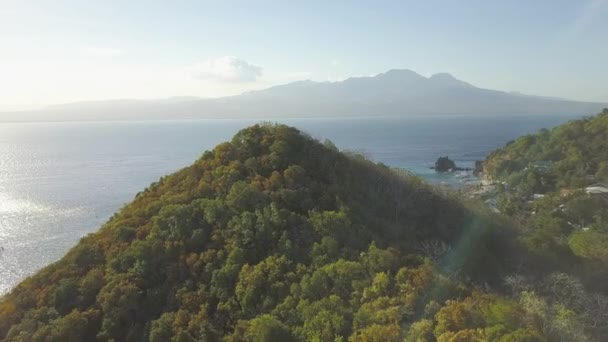 Mountain silhouette on horizon and green hill on sea landscape. View from above flying drone green highland on blue sea and mountain landscape.