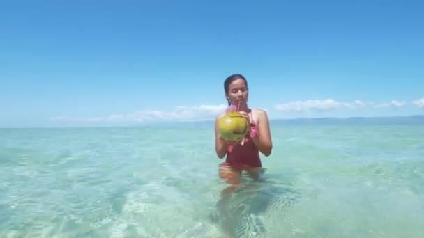 Pretty asian girl drinks coconut and smiles bathing in ocean on Philippines.