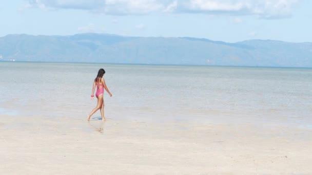 Ázsiai lány fürdőruhát sétál óceán strand hegyek háttérben a szigeten.