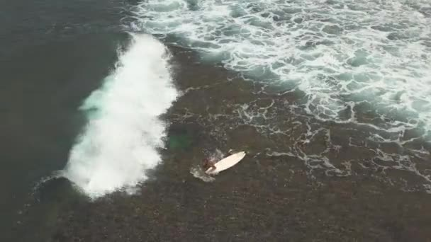 Top down view of a surfer carried away by breaking waves towards the seashore.
