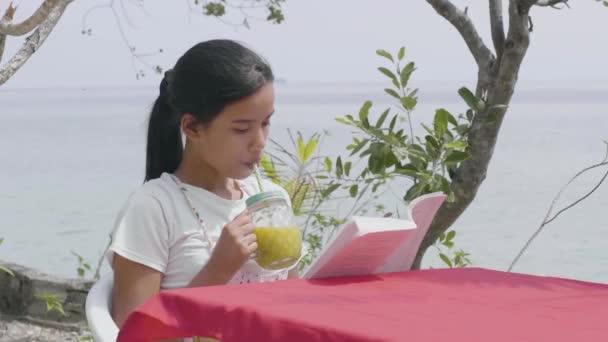 Žena se stresem volný čas těší studené občerstvení při čtení knihy.
