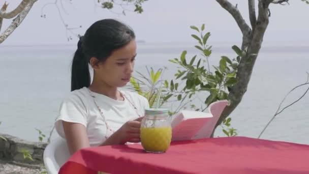 hübsche Frau liest ein Buch und trinkt im Sommer Saft auf dem Tisch am Meer