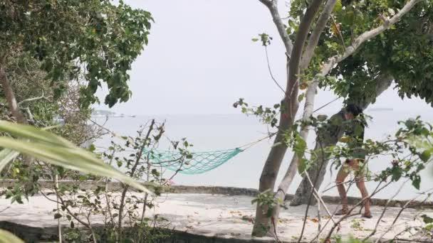 Sexy žena v plavkách kráčející po pláži a sedět na houpací síti.