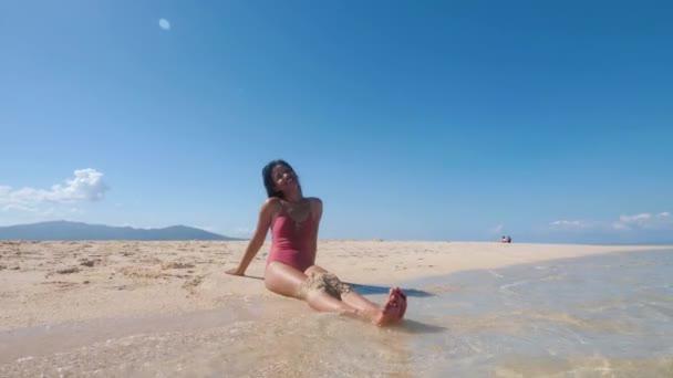 Csinos ázsiai lány fürdőruhában napozás ül az óceán homokos strandján és mosolyog.
