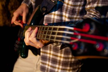 Electric bass guitar player, closeup photo with soft selective focus on dark
