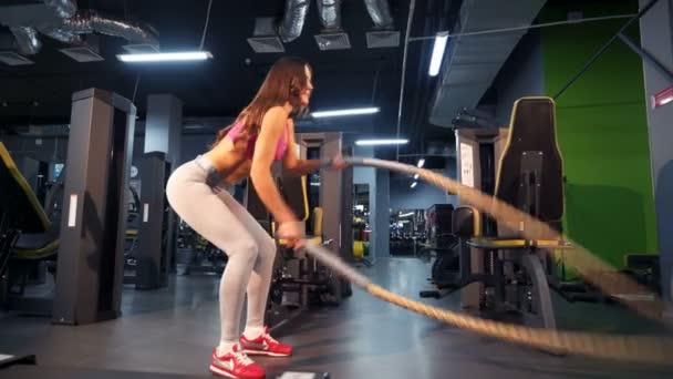 Bitva lana relace. Atraktivní mladá a sportovní dívka pomocí lana trénink v tělocvičně.