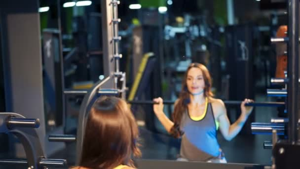 Fitness woman doing sit-ups with a barbell in the gym. Smith machine in the gym. Ideal female figure.