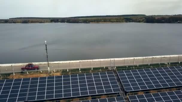 Solární panely poblíž řeky. Elektrárna. Modrá solární panely. Alternativní zdroj elektrické energie. Sluneční farma.
