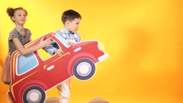Bambini divertenti stanno giocando con una grande macchina rossa. Sfondo decorativo. Riprese in studio dei bambini