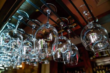 Glasses of wine hanging above a bar rack in restaurant.