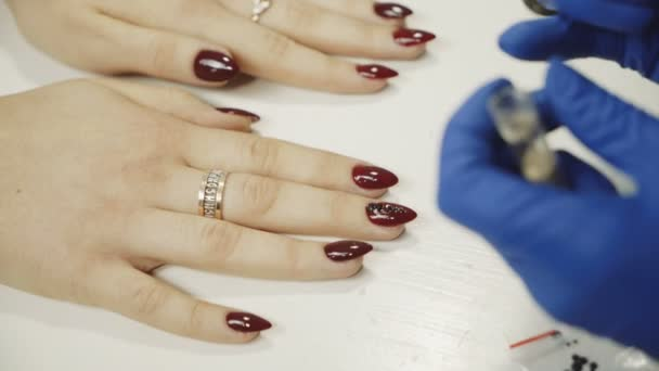 Maniküre, die roten Nagellack aufträgt. Strass auf Nägeln