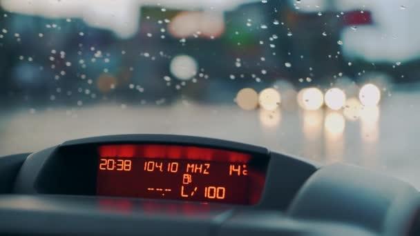 Dešťové kapky padají na čelní sklo auta. Pohled dovnitř. Přístrojové. Detail