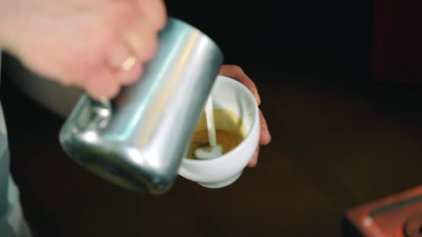 Barista pouring milk in coffee cup for making latte art.slow motion shot. Art of making cappuccino in a cup