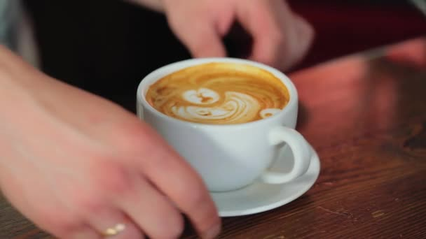 Barista makes a drawing on coffee. Art of making cappuccino in a cup.