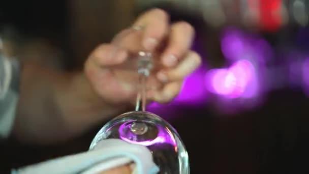 Barman čistí sklo. Hezký barman leští sklenici sklenice. Detailní záběr