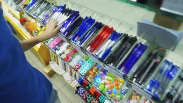 Chlapec v šablonu koupí pero. Zpátky do školy koncept