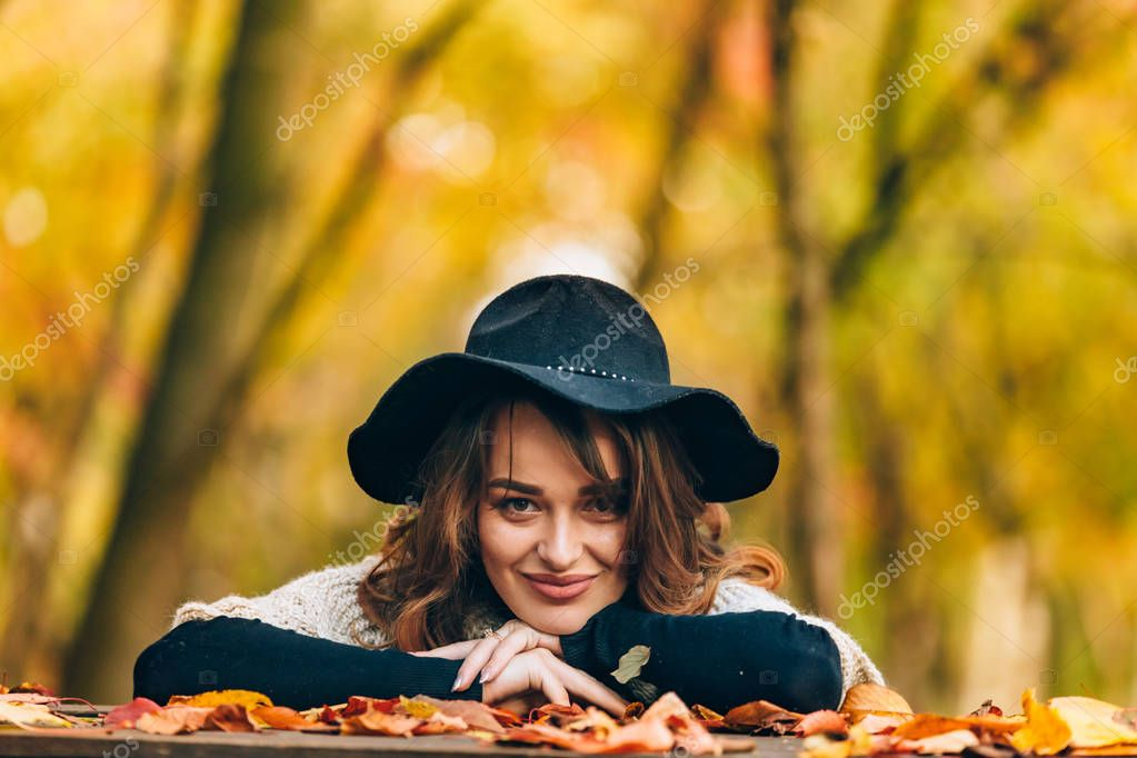 brown-haired woman in hat smiles and bases her hands on the table with foliage in the park