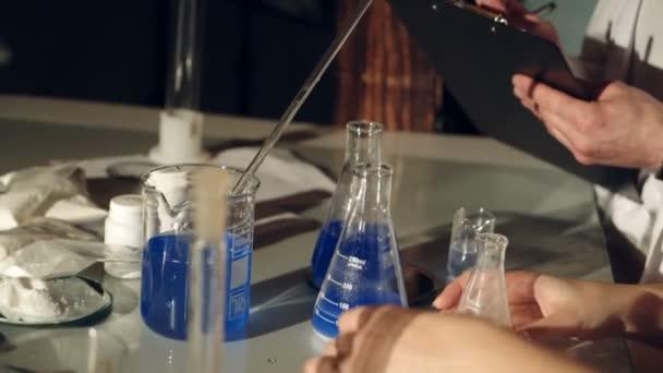 A tudósok vizsgálata folyadékok főzőpoharak. Kísérletek, a kémia laborban. Közeli kép: