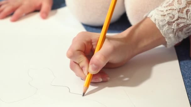 Female hands with a graphite pencil. Young woman learns to draw.