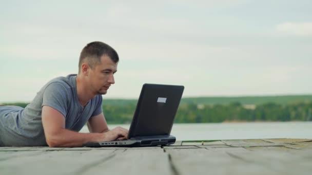 Mann, der draußen am Laptop arbeitet. Holzsteg im See