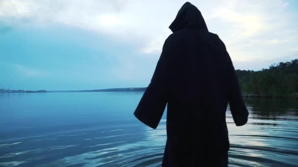 Děsivá postava v černém plášti v řece. Halloween kostým