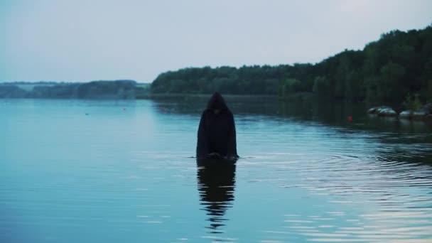 Ghost žena v venkovní vodě. Děsivá postava v černém plášti