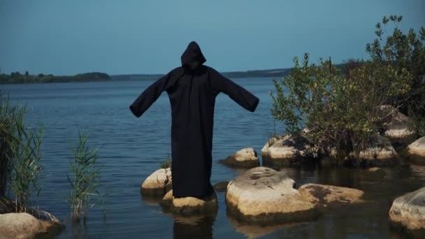 Žena ďábel v černé kápi a kapuce na kamenech u řeky. Halloween kostým