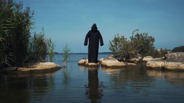 In piedi terribile demone nel fiume. Figura spaventosa in mantello nero.