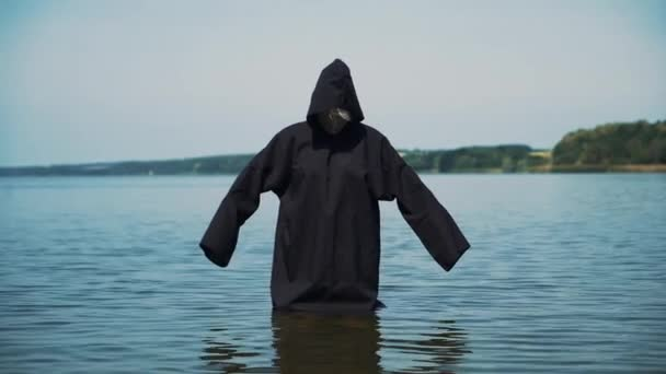 Scary figure in black mantle in the river. Halloween costume