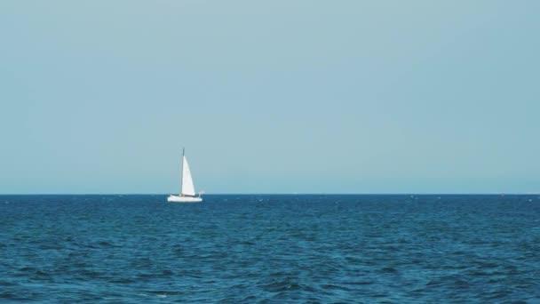 Jachta pluje na otevřeném moři za slunečného dne. Luxusní jachta křižující po moři. Plně rozvinuté plachty