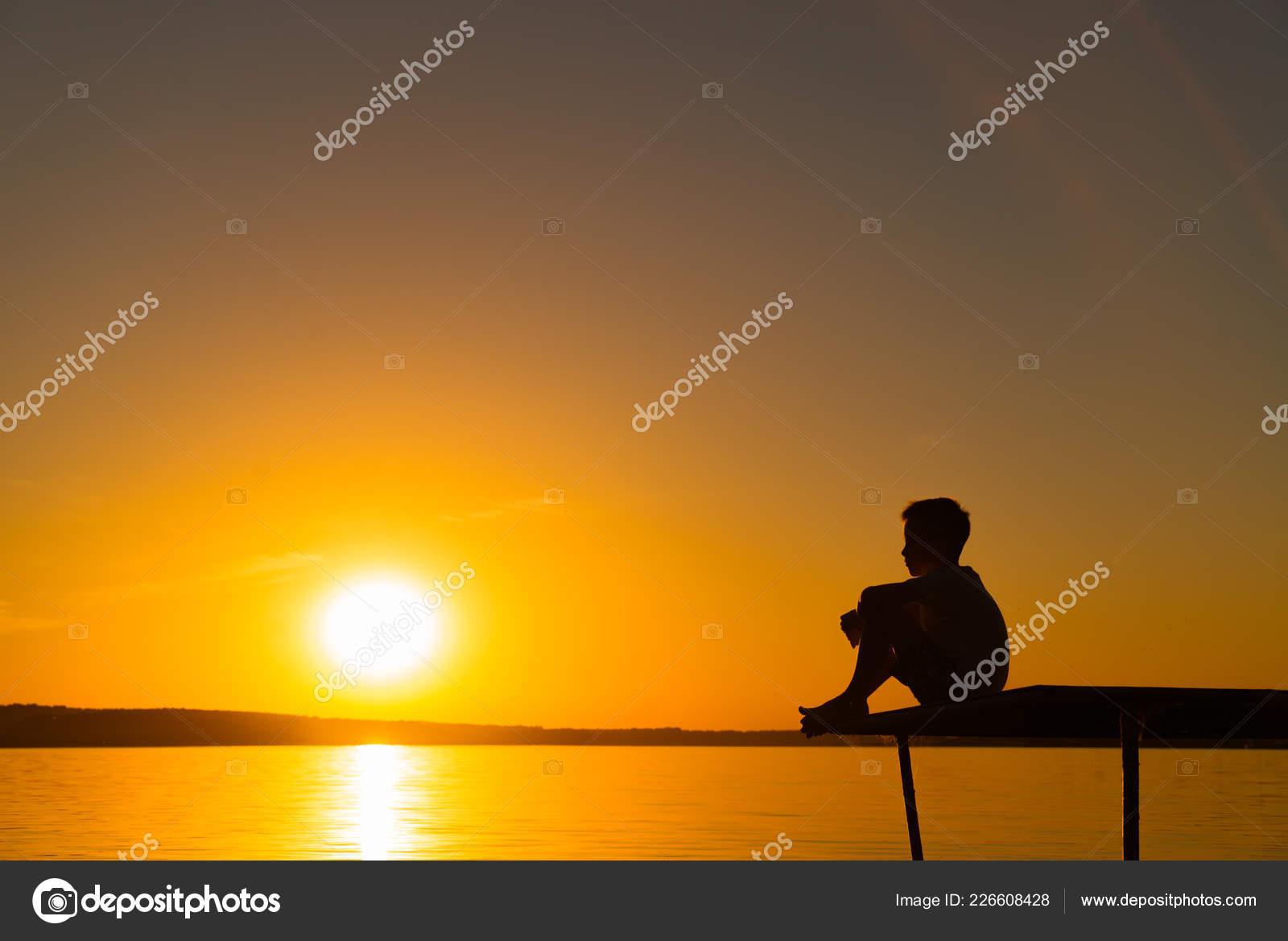 Silhouette little boy sitting bridge river sky sunset lonely boy stock photo